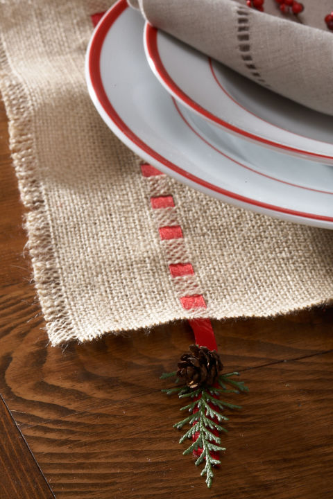 Lay wide burlap strips across the table, letting them hang about 6 inches over the sides. Pull out six strands of burlap about 2 inches from each edge, then thread 1?4-inch satin ribbon through every 3?4 inch.