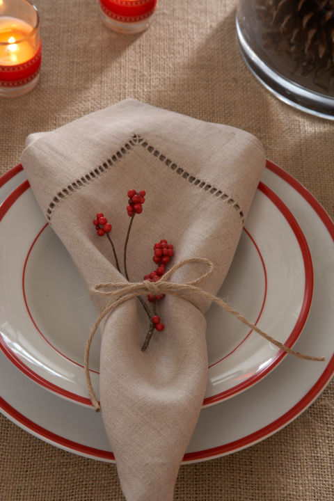 Gather hemstitched linen napkins, tie them with twine, and tuck a few sprigs of artificial cranberry in the middle.