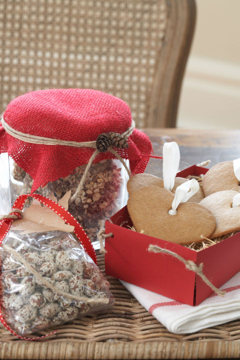 Pour spiced nuts into clear bags and finish off with ribbon, twine and a tree-shaped tag cut from kraft paper. Cover a jar of peanut brittle with red burlap, add twine and glue on pinecones. Buy gingersnaps with precut holes, string with ribbon.