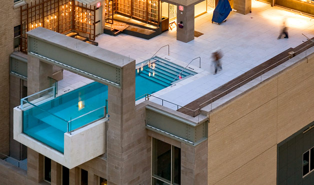 this architecturally daring pool designed by architexas sits atop the joule hotel in dallas texas ten stories above the ground the pool projects eight