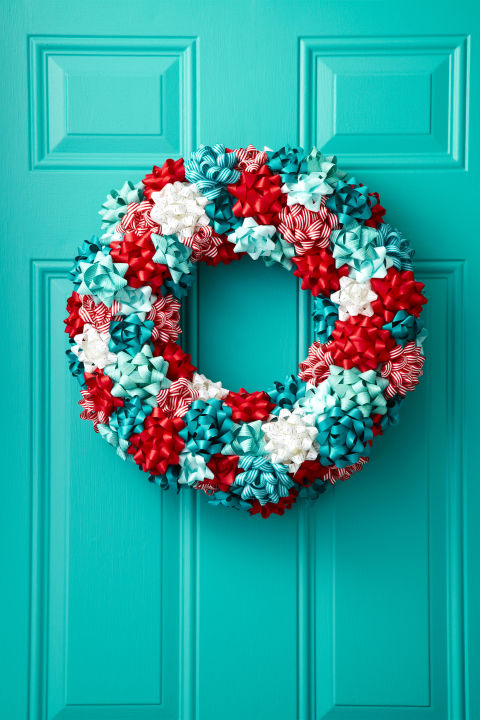 """To turn store-bought bows into a jolly wreath, first attach a loop of floral wire (for hanging) around a 16"""" Styrofoam wreath form. Then, hot glue gift bows to the front and sides of the form. Keep it festive with a classic red-and white combo or mix in powder blue for a wintry look. What you'll need:Styrofoam wreath ($12; amazon.com); Gift bows ($11; amazon.com)"""